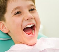 Photo of youngster with his mouth wide open during checkup at the dentist's